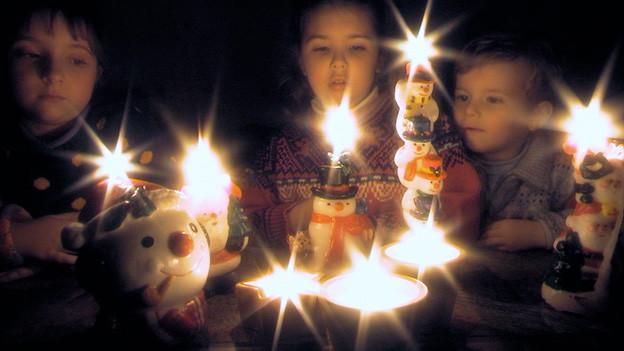 Leuchtende Kinderaugen im Kerzenlicht.