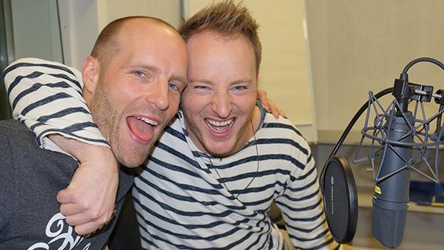 Zwei Männer ziehen vor einem Mikrofon Grimassen.
