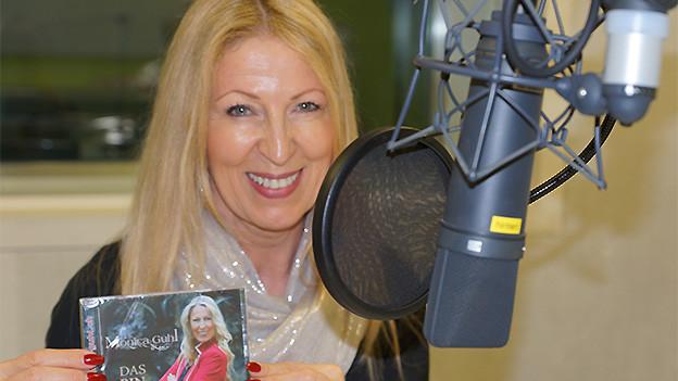 Eine Frau mit langen blonden Haaren in einem Radiostudio.