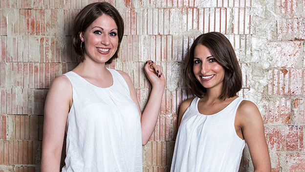 Zwei junge Frauen stehen vor einer Mauer.
