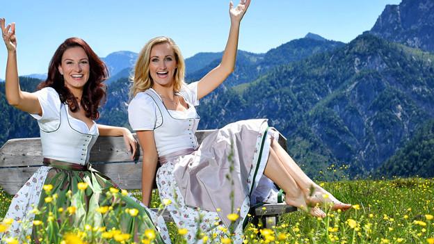 Zwei junge Frauen auf einer Wiese.