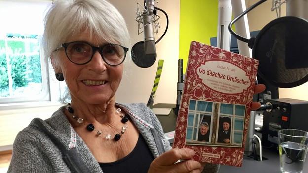 Eine Frau in einem Radiostudio zeigt ein Buch.