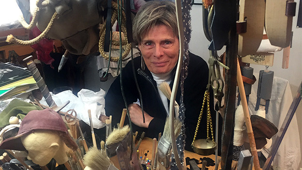 Eine Frau sitzt in einem Atelier voller verschiedener Materialien.