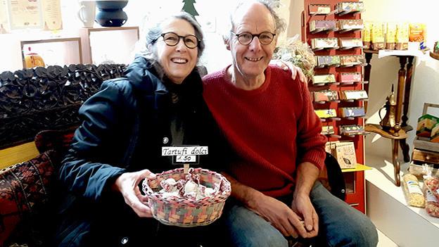 Eine Frau und ein Mann an einem Marktstand mit Gemüse.