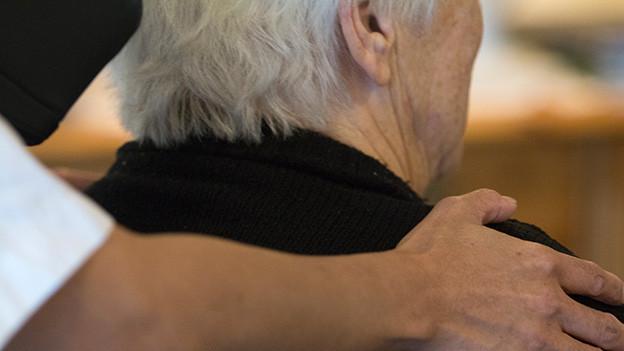 Die Hand eines Pflegers auf der Schulter eines alten Patienten.