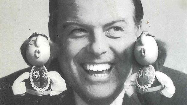 Ein lachender Mann hält seinen Kopf zwischen zwei kleine pfeifende Puppen.