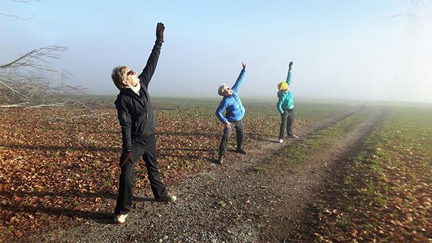 Drei Frauen bei Körperübungen auf einem Naturpfad.