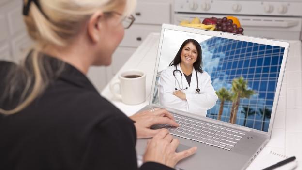 Frau am Computer, auf dem Bildschirm ist eine Ärztin zu sehen.