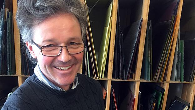Ein lachender Mann mit wilden Haaren und Brille.
