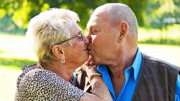 Frau und Mann küssen sich.
