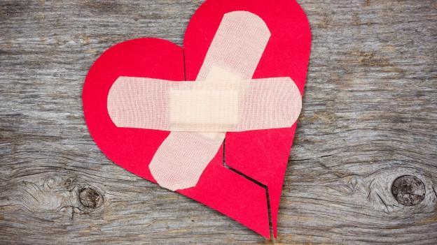 Gebrochenes Herz wird mit Pflästerli zusammengeklebt.