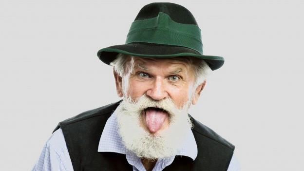 Ein älterer Mann mit Bart streckt seine Zunge heraus.