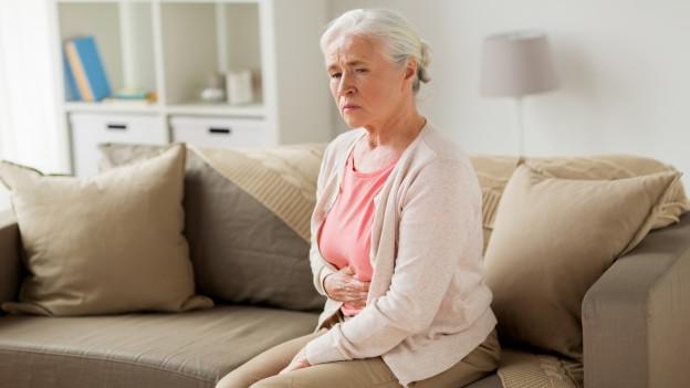 Frau mit schmerzverzerrtem Gesicht hält ihren Bauch.