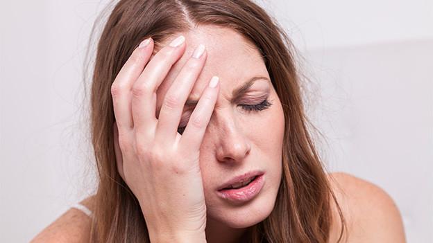 Eine Frau hält sich mit schmerzverzerrtem Gesicht eine Hand an den Kopf.