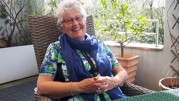 Eine lachende Frau sitzt auf der Dachterrasse an einem Tisch.