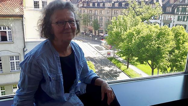 Eine Frau sitzt vor einem grossen Fenster mit Blick auf Häuser und Strassen.