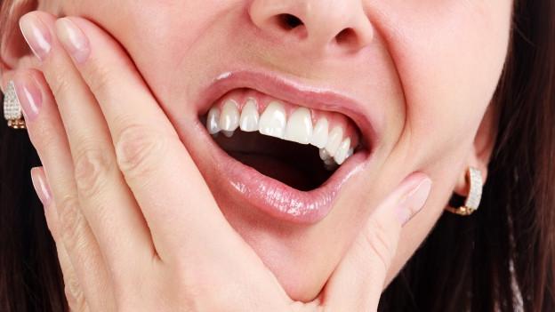 Frau hält ihren schmerzenden Mund.