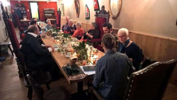 Menschen an Tisch mit hohen Stühlen.