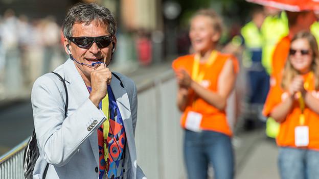 Ein Mann am Rande einer Laufstrecke spricht in ein Mikrofon.