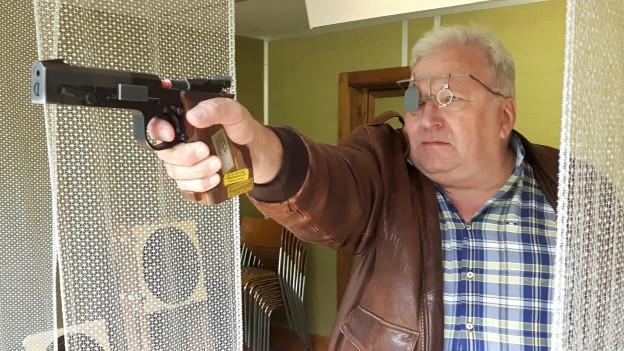 Ewald Kessler hält eine Pistole in der Hand und zielt.