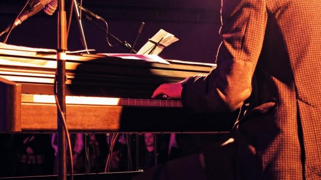 Jemand spielt in einer Bar Klavier.