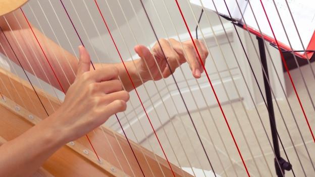 Eine Person spielt auf einer Harfe.