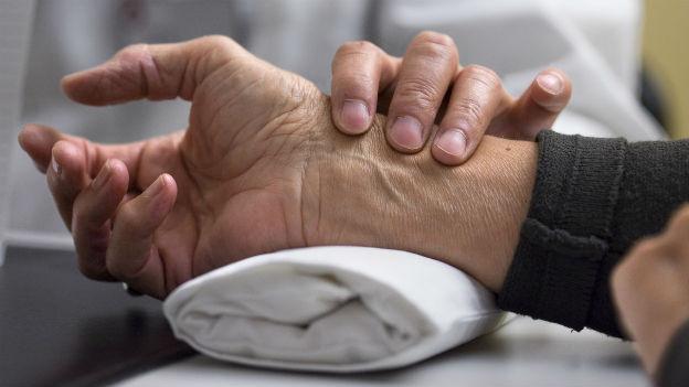 Ärztin nimmt den Puls beim Patienten.