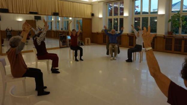 Menschen auf Stühlen tanzen in Ballettsaal.