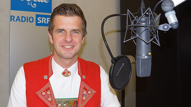 Ein junger Mann in Appenzeller Tracht im Radiostudio.