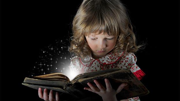 Ein Mädchen mit einem grossen offenen Buch.
