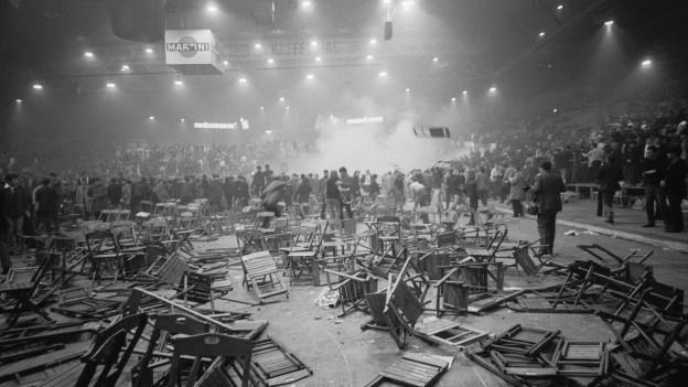 Schwarzweiss-Aufnahme einer Szene aus 1968: Stühle liegen kreuz und quer auf dem Boden.