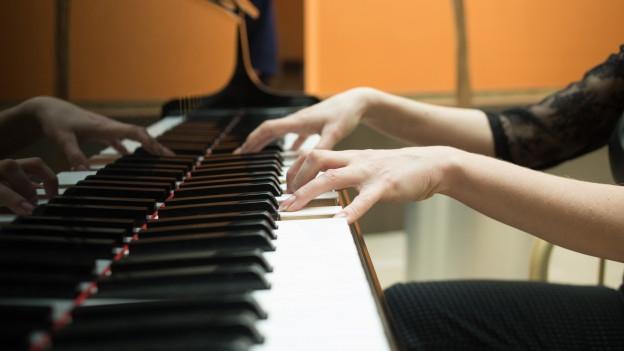 Klavierspielerin mit Fokus auf Hände und Tasten.