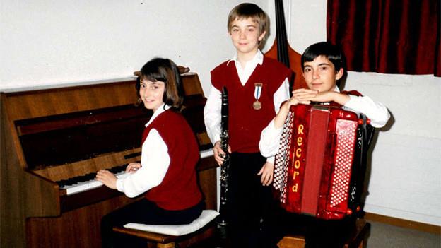 Drei musizierende Kinder.