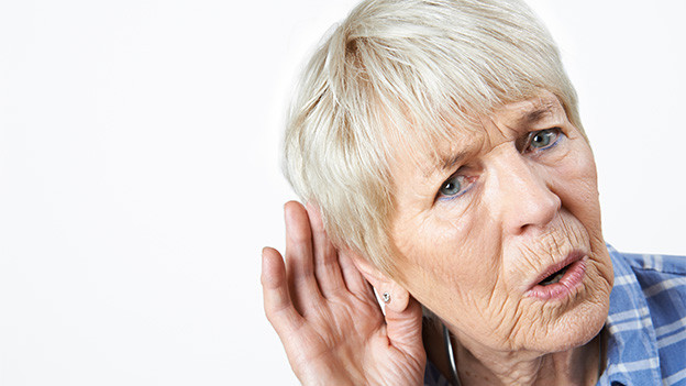 Eine Frau formt mit ihrer Hand eine Muschel an ihrem Ohr.