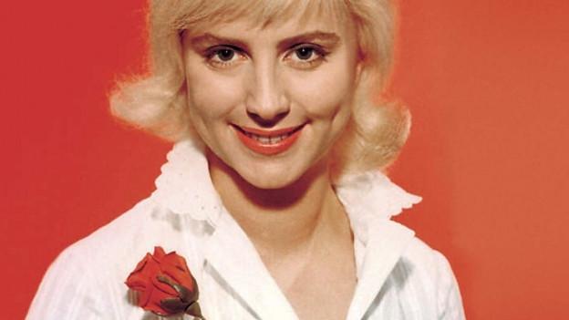 Blonde Frau vor rotem Hintergrund.