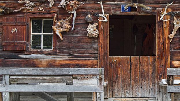 Eine Holzbank vor einer alten Holzhütte.