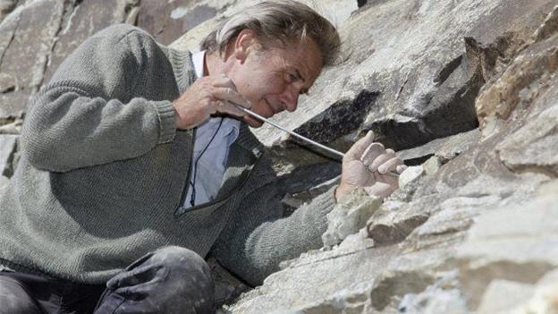 Ein Strahler legt Mineralien frei.