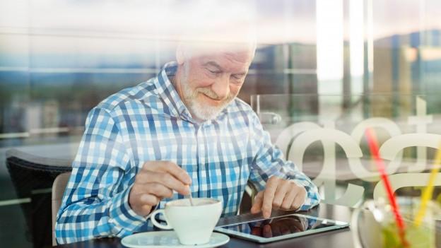 Ein Mann tippt in einem Café auf seinem Tablet herum.