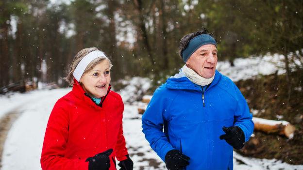 Frau und Mann joggend im Wald im Winter.