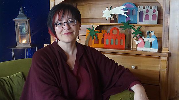 Eine dunkelhaarige Frau mit Brille auf einem grünen Sofa.