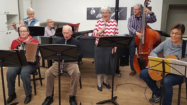 Eine Gruppe älterer Menschen beim gemeinsamen Singen und Musizieren.