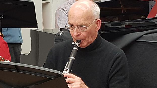 Ein älterer Mann spielt Klarinette.