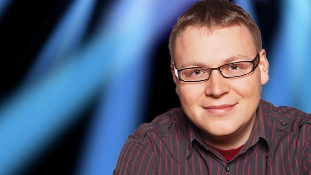 Ein Mann mit Brille und gestreiftem Hemd.