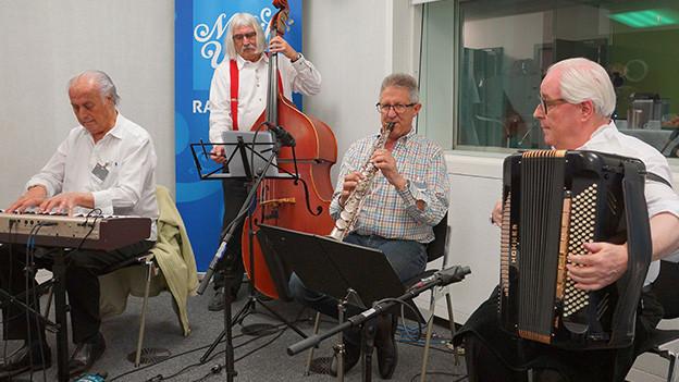 Vier Volksmusikanten in einem Radiostudio.