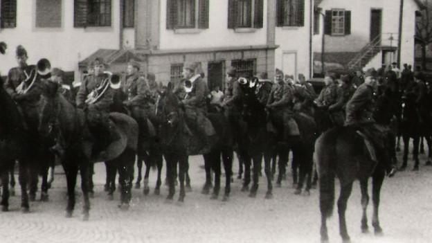 Männer in Uniform sitzen auf Pferden und halten ihre Musikinstrumente in der Hand.