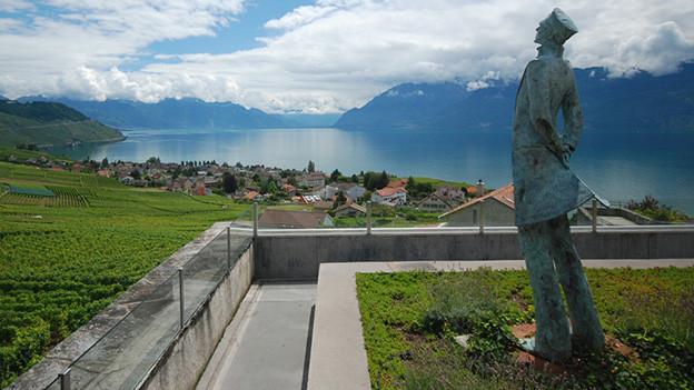 Eine schlanke Statue auf einem Hügel mit Blick auf einen See.
