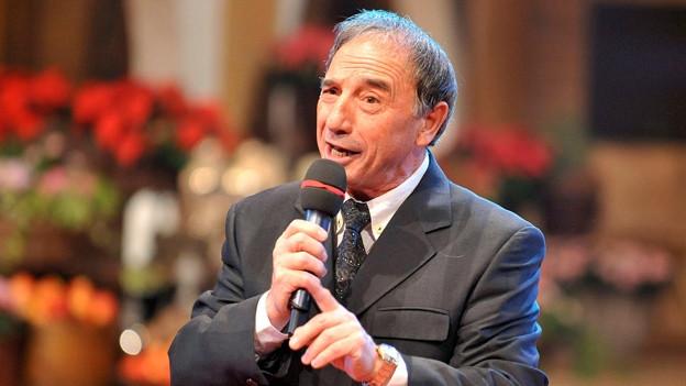 Rocco Granata singt mit einem Mikrophon in der Hand.