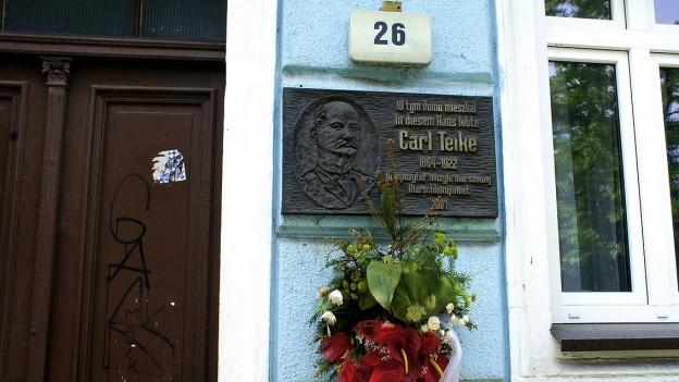 Eine Gedenktafel hängt an einer Hauswand.