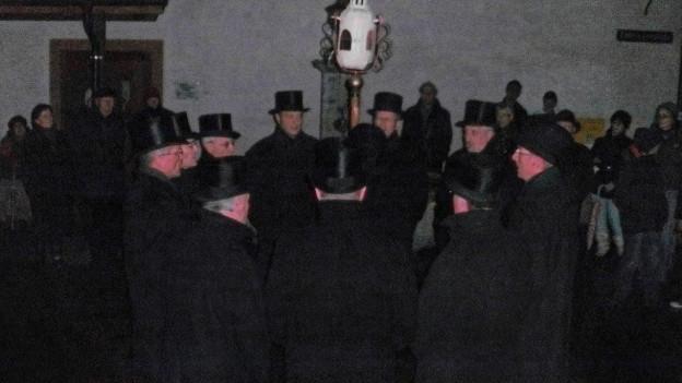 Männer stehen im Dunkeln um einen Brunnen.