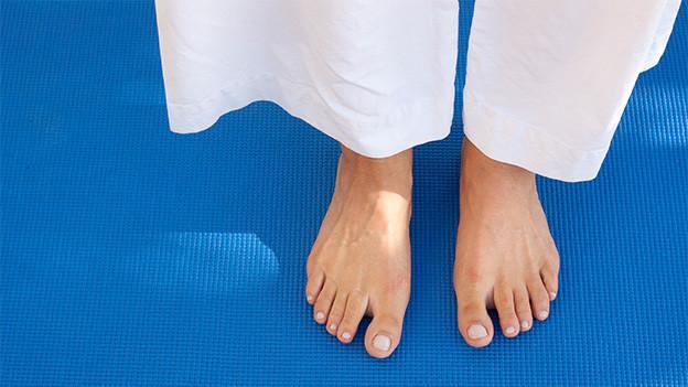 Zwei nackte Füsse auf einer Gymnastikmatte.